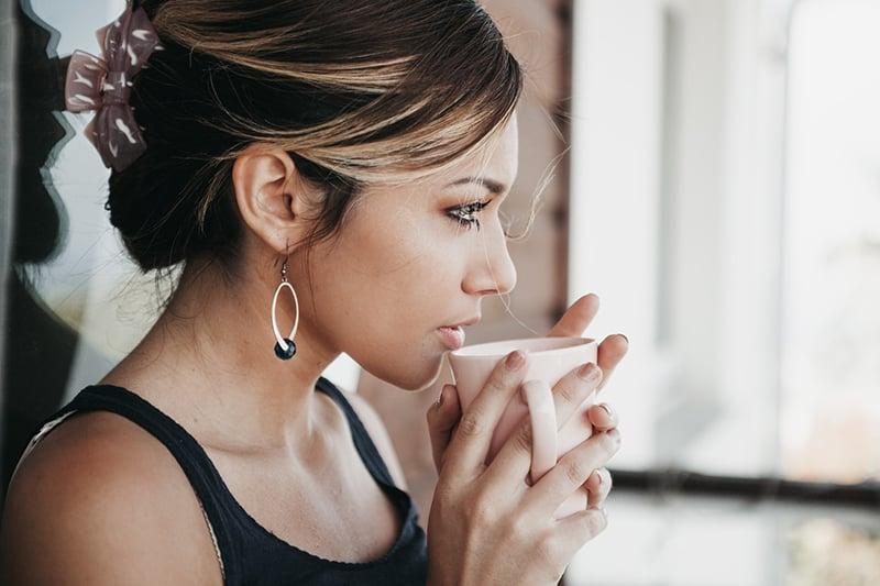 eine Frau, die gerade Kaffee trinken will und nachdenklich aussieht