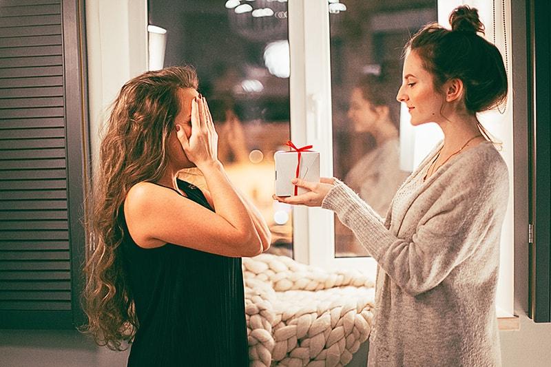 eine Frau, die ihre Augen vor einer Freundin bedeckt, die ein Geschenk hält, während sie in der Nähe des Fensters steht