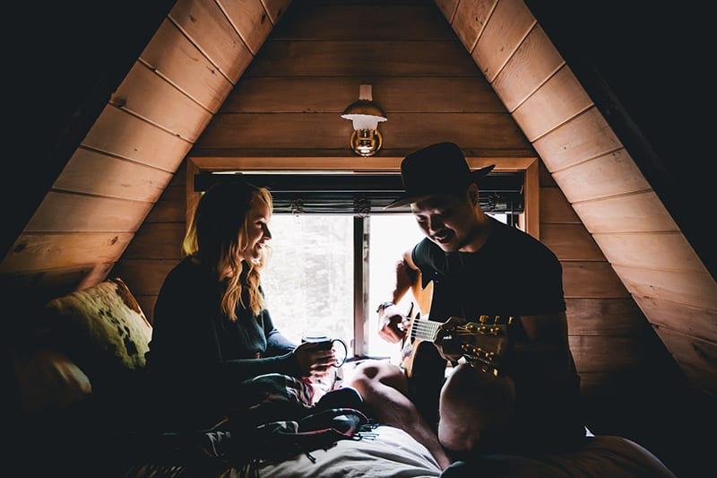 Eine Frau hört ihrem Freund zu, wie er auf dem Bett Gitarre spielt