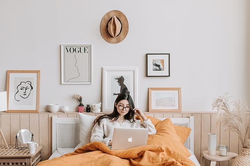 eine Frau, die im Internet mit einem Laptop im Bett recherchiert