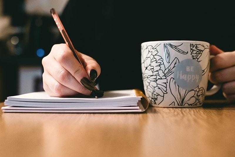 eine Frau, die in ein Notizbuch schreibt und einen Keramikbecher hält
