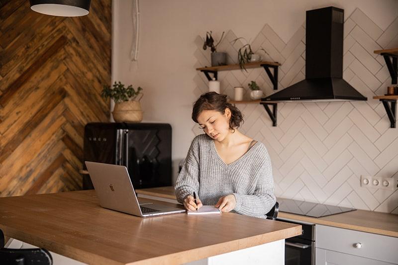 eine Frau, die in ein Notizbuch in der Küche schreibt