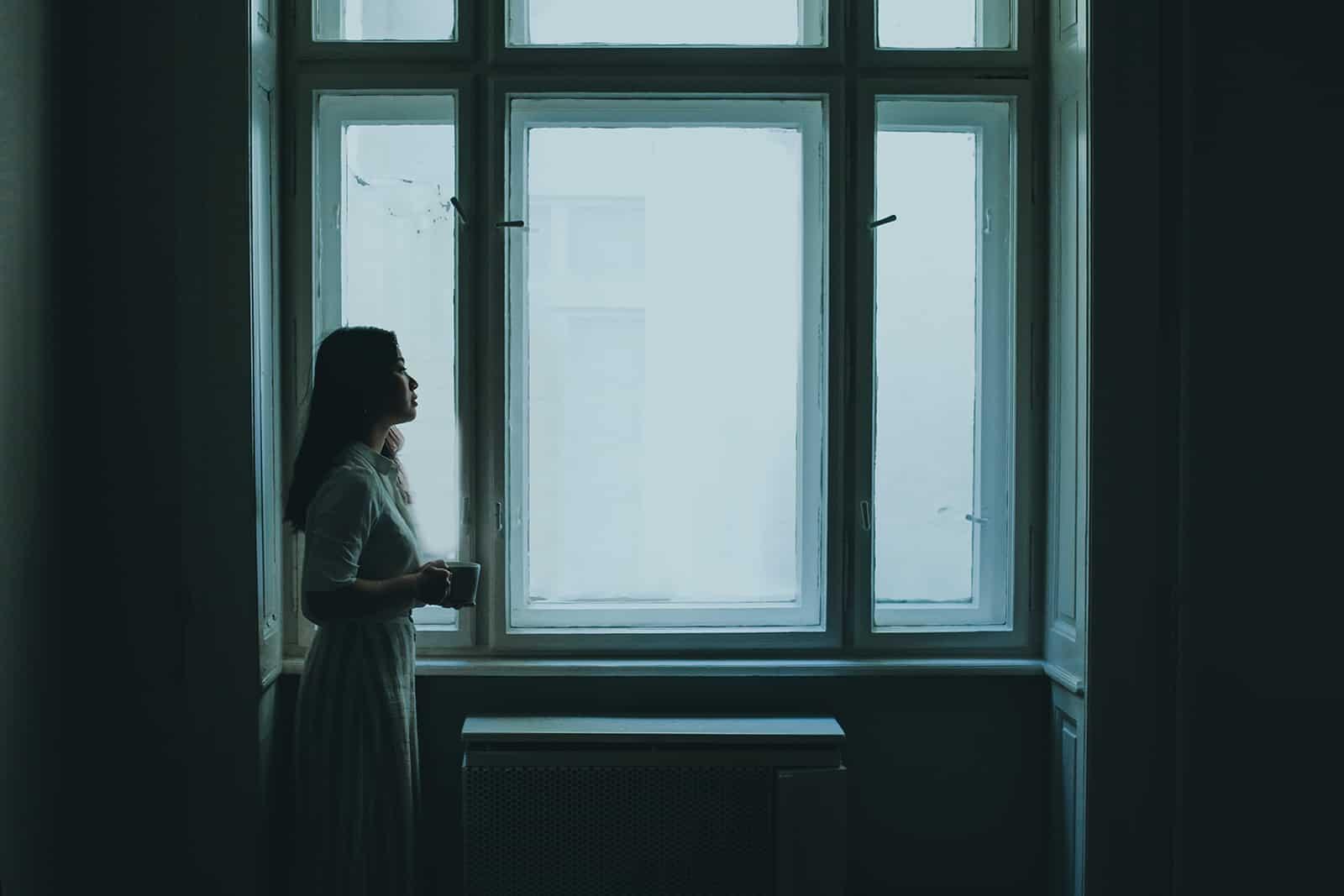 eine Frau, die in einem dunklen Raum neben dem Fenster steht
