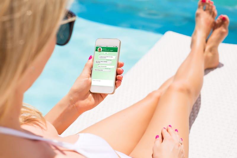 Eine Frau, die mit einem Freund auf ihrem Smartphone eine Nachricht sendet, während sie in der Nähe des Schwimmbades sitzt
