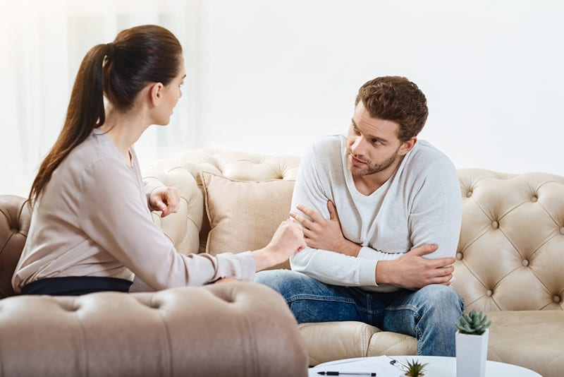 eine Frau, die mit einem Mann spricht, während sie auf der Couch sitzt