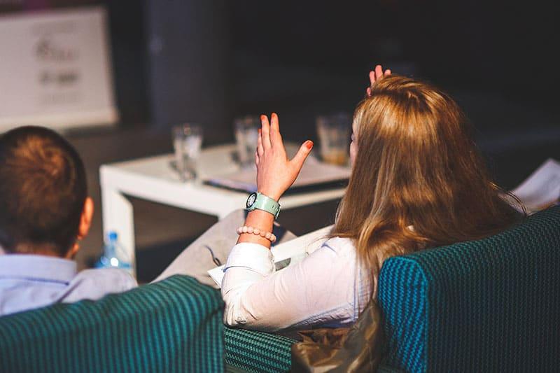 eine Frau, die mit einem Mann streitet und mit den Händen gestikuliert, während sie auf der Couch sitzt