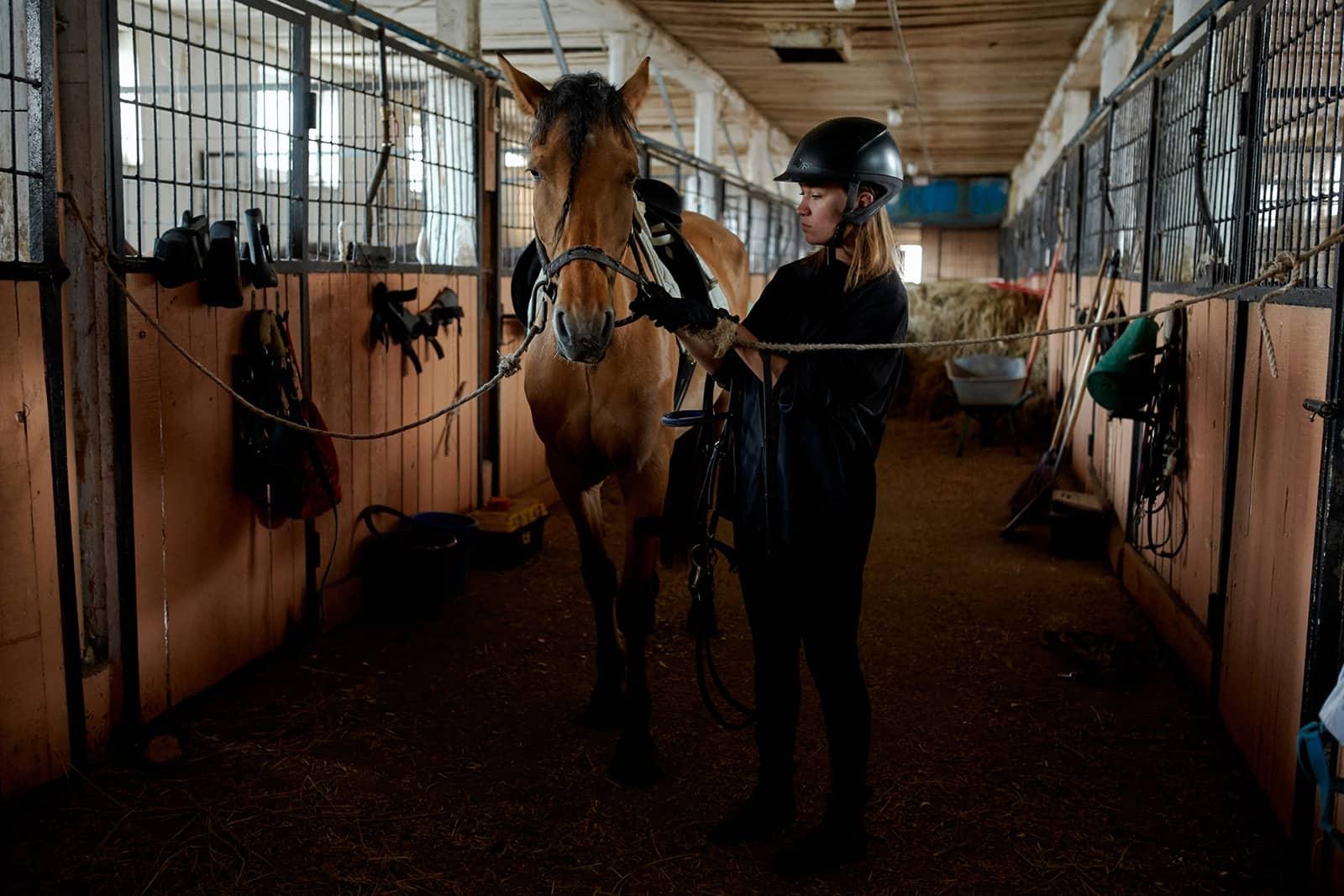 eine Frau, die mit einem Pferd in einem Stall steht