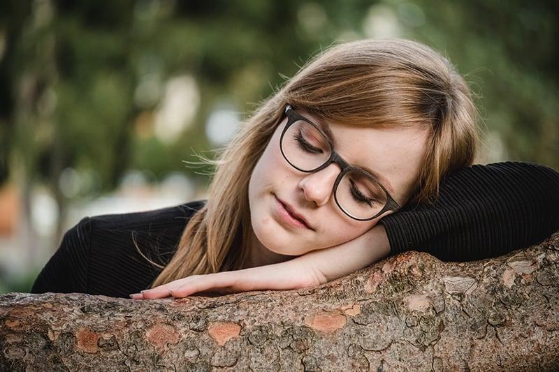 eine Frau, die sich an den Baum stützt und nachdenkt