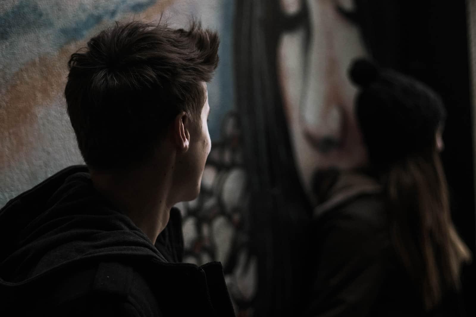 eine Frau, die sich von einem Mann abwendet, der neben ihr in der Nähe der Graffiti-Wand steht