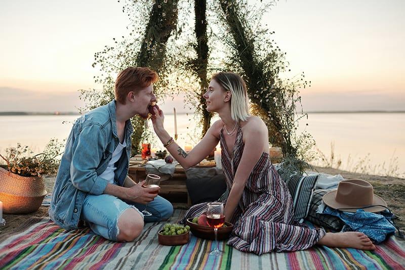 eine Frau, die ihren Freund mit Früchten füttert, während sie während des Sonnenuntergangs am Strand sitzt