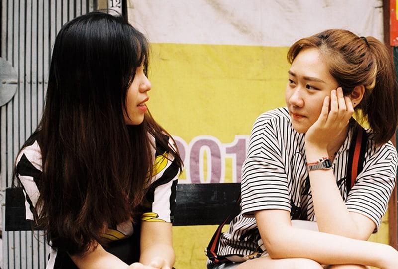 eine Frau, die mit ihrer Freundin spricht, während sie auf der Bank sitzt