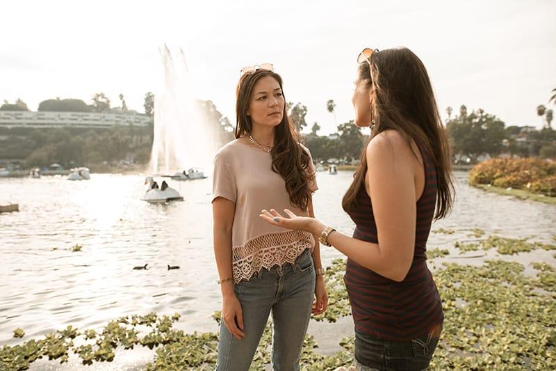 Eine Frau in einem beigen Haus hört ihrer Freundin aufmerksam zu, während sie in der Nähe des Sees steht