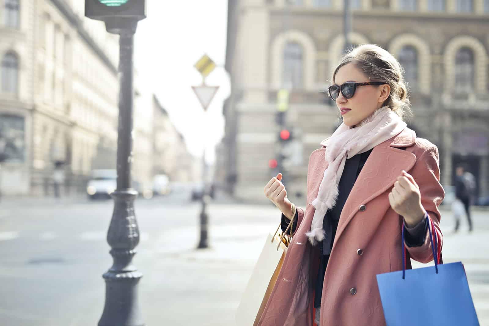 eine Frau in einem rosa Mantel, der Einkaufstaschen hält, die auf dem Bürgersteig stehen