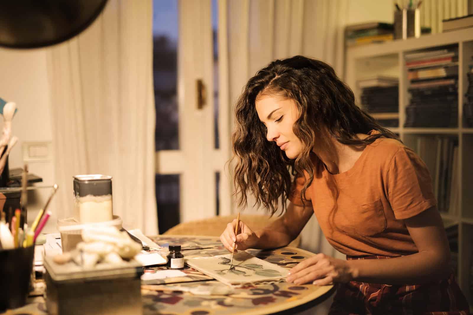 eine Frau, die auf einem Papier am Tisch malt