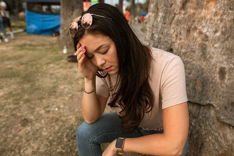 eine Frau mit Kopfschmerzen, die ihren Kopf berührt, während sie in der Nähe des Baumes sitzt