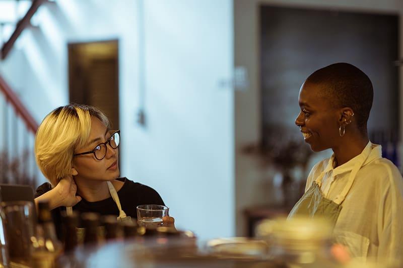 eine Frau mit blonden Haaren, die sorgfältig lächelnde Freundin zuhört, während sie in der Nähe der Bar steht