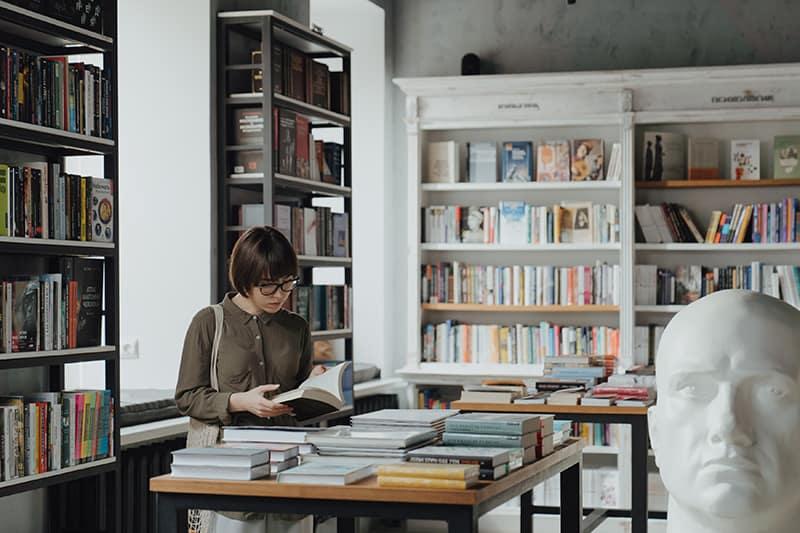 eine Frau, die ein Buch hält, während sie in einem Buchladen steht