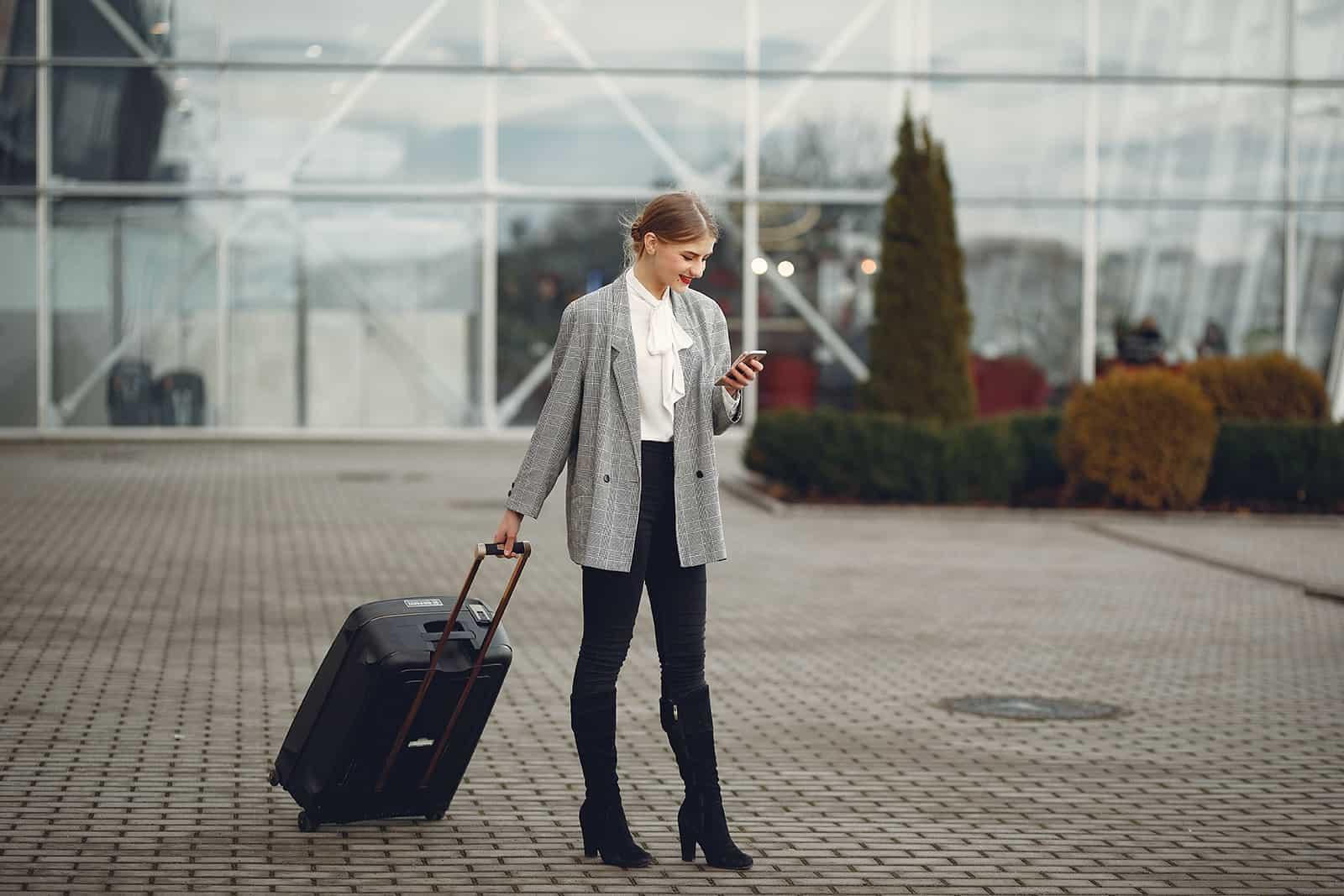 eine Frau mit einem Koffer SMS auf einem Smartphone vor dem Flughafen stehen