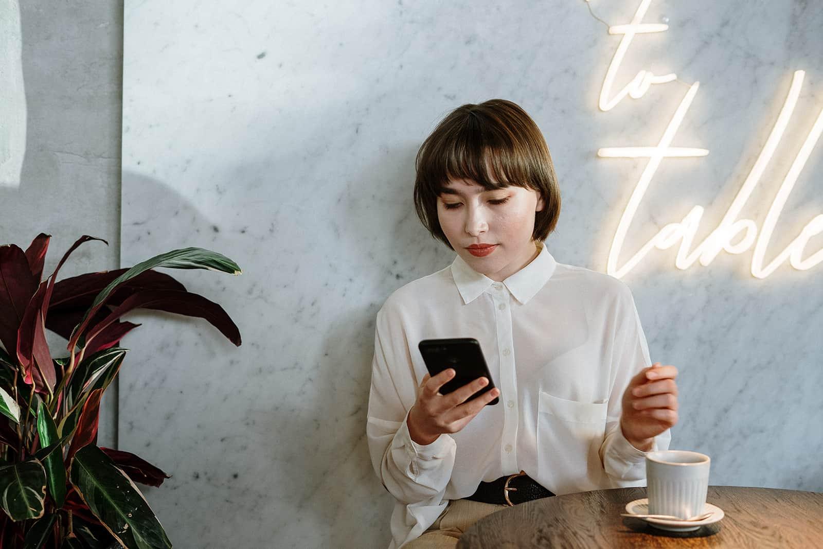 eine Frau, die ein Smartphone benutzt, während sie alleine in einem Café sitzt