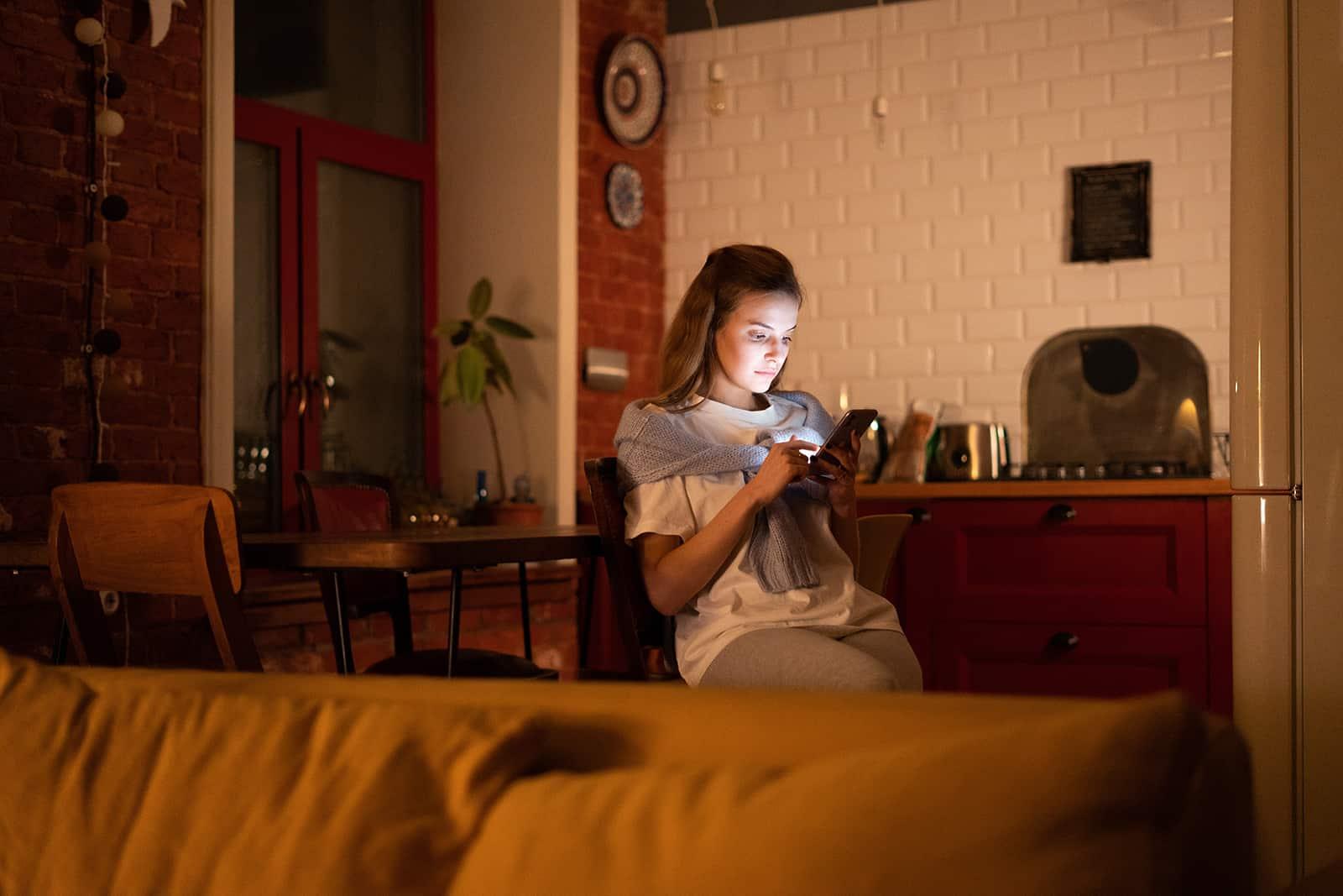 eine Frau, die ein Smartphone benutzt, während sie alleine in einem Esszimmer sitzt