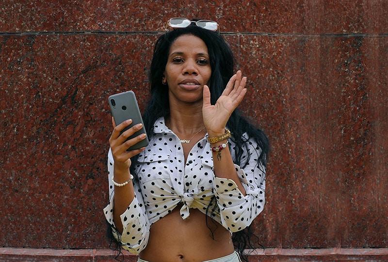 eine Frau, die ein Smartphone hält und nahe der braunen Wand steht