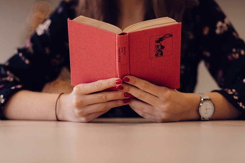 eine Frau, die ein rotes Buch hält, während sie am Tisch sitzt