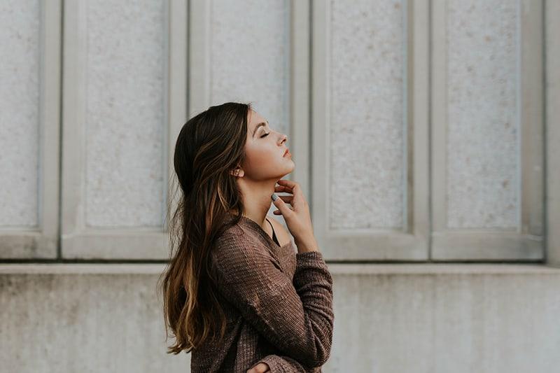 eine Frau mit geschlossenen Augen, die den Hals mit der Hand berührt, die nahe der grauen Wand steht