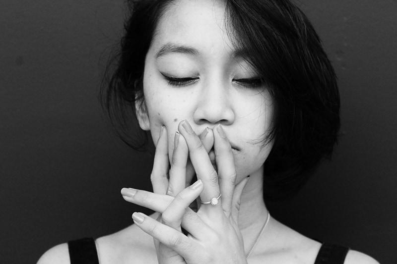 eine Frau mit geschlossenen Augen, die mit den Händen die Lippen berührt