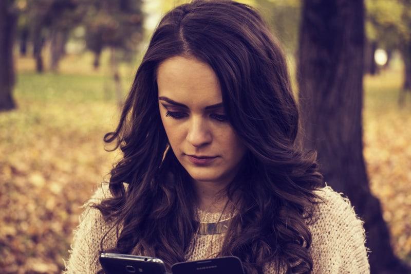 eine Frau mit langen braunen Haaren, die ein Smartphone beim Stehen im Park betrachtet