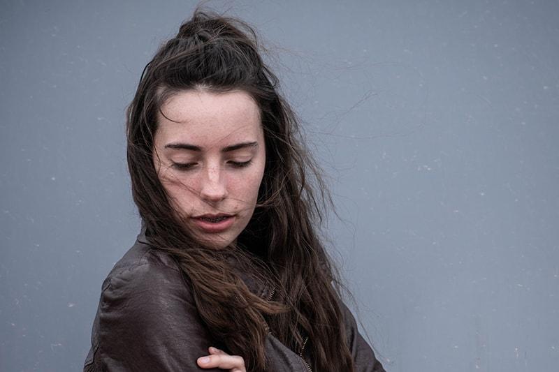 eine Frau mit langen braunen Haaren, die nach unten schaut, während sie im Wind steht