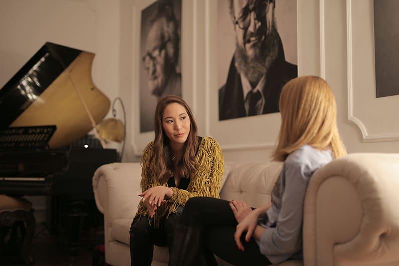eine Frau mit langen braunen Haaren, die mit einer Freundin spricht, während sie auf der Couch sitzt