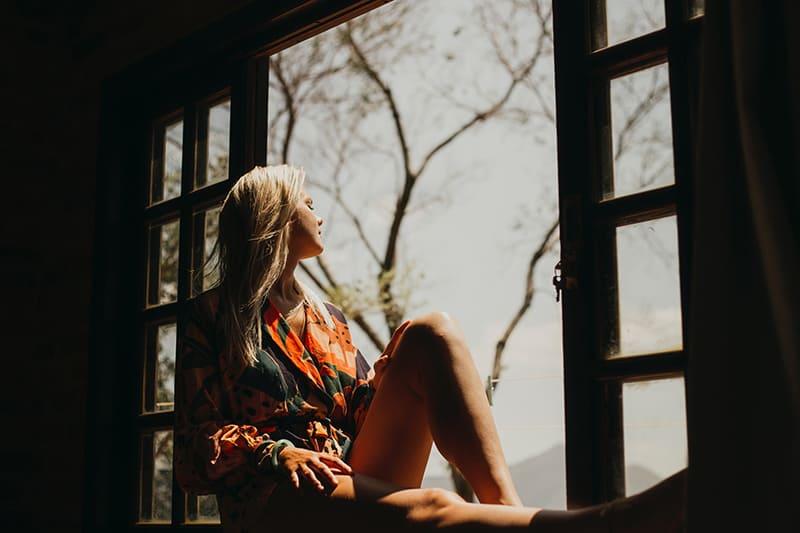 eine Frau, die auf der Fensterbank sitzt und durch das Fenster schaut