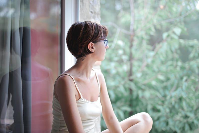 eine Frau, die auf der Fensterbank sitzt und nachdenkt