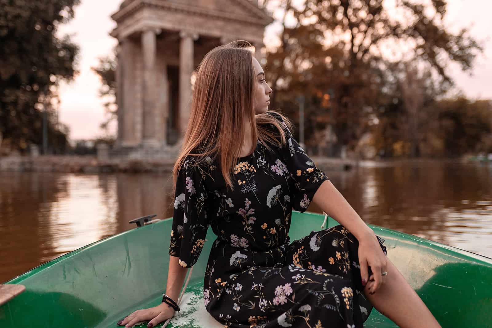 eine Frau, die auf einem Boot sitzt und zur Seite schaut
