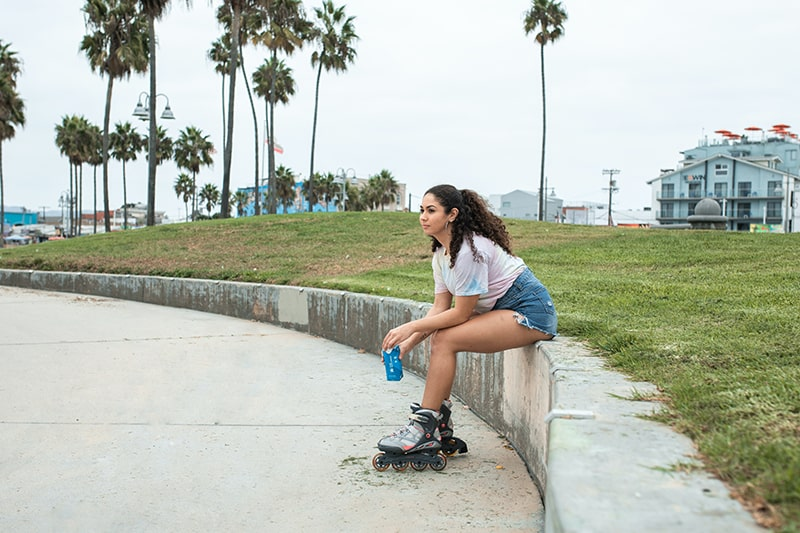 eine Frau, die auf einer Betonwand mit Rollschuhen auf ihren Beinen sitzt