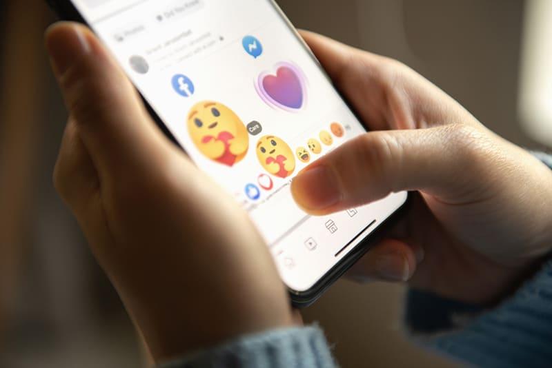 Eine Person, die während des Chats Emoji auf dem Smartphone auswählt