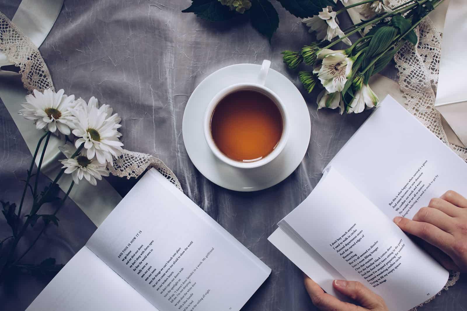 eine Person, die ein Buch neben dem Tee und den Blumen liest
