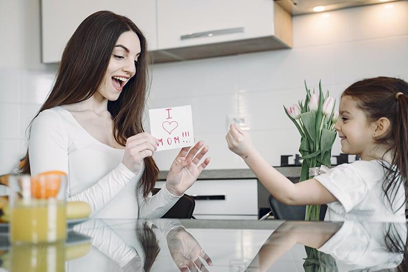 eine Tochter, die ihrer lächelnden Mutter in der Küche eine Notiz gibt
