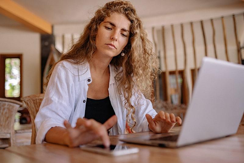 eine beschäftigte Frau, die ihr Smartphone berührt, während sie vor einem Laptop sitzt