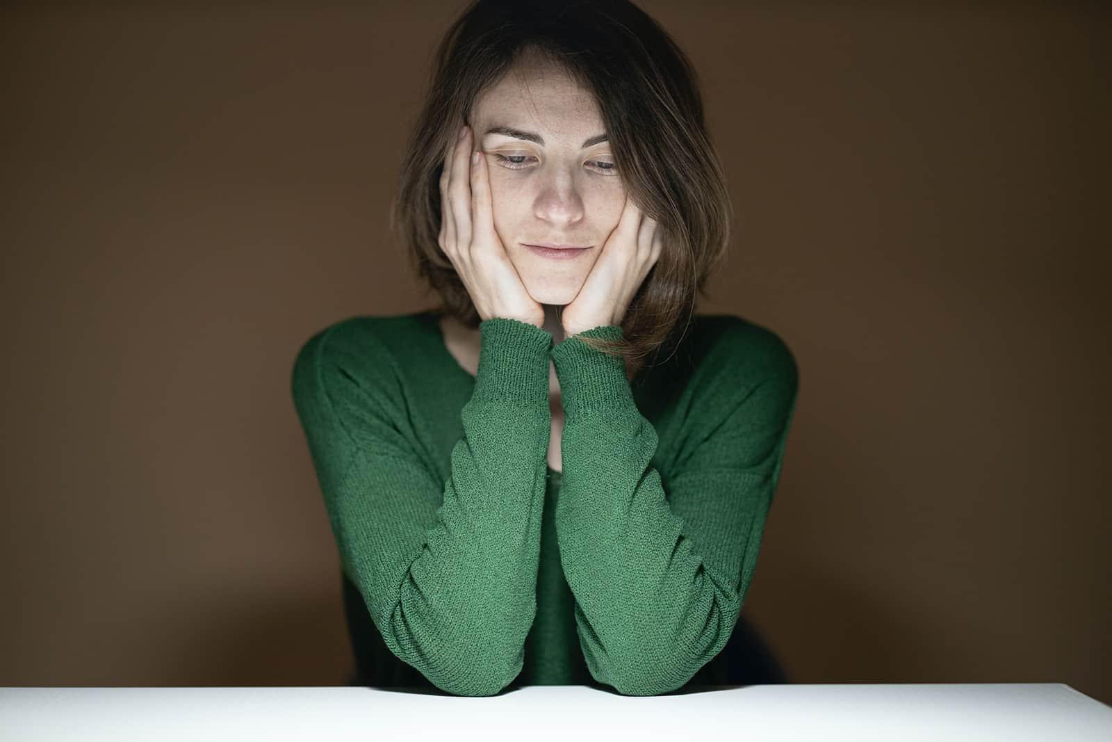 eine depressive Frau, die am Tisch sitzt und nach unten schaut