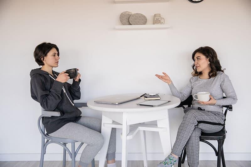 eine ernsthafte Frau, die ihrer lächelnden Freundin zuhört, während sie zusammen Kaffee trinkt