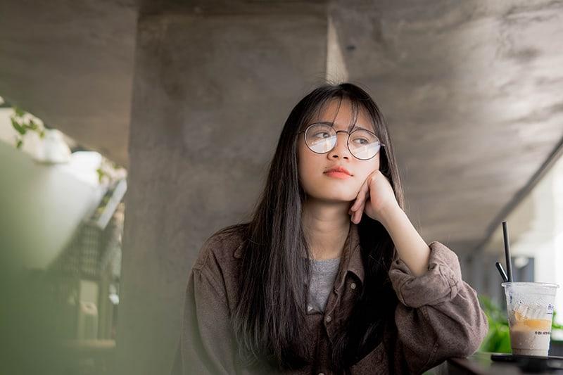eine geduldige Frau, die den Kopf auf ihre Hand stützt und im Café sitzt
