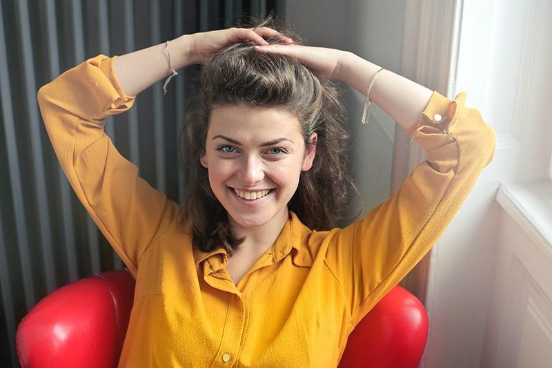 eine lächelnde Frau, die Haare mit den Händen berührt, während sie in einem roten Sessel sitzt