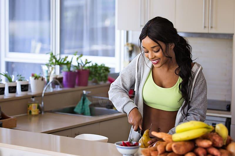 eine lächelnde Frau, die die Frucht in der Küche schneidet
