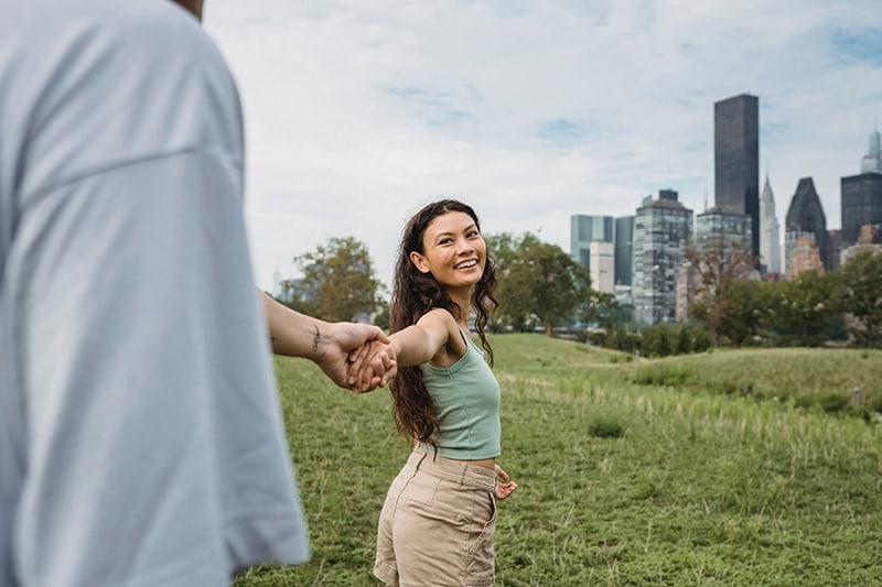 eine lächelnde Frau, die die Hand ihres Freundes hält, während sie im Park geht