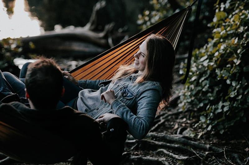 eine lächelnde Frau, die in einer Hängematte mit einem Mann im Wald liegt
