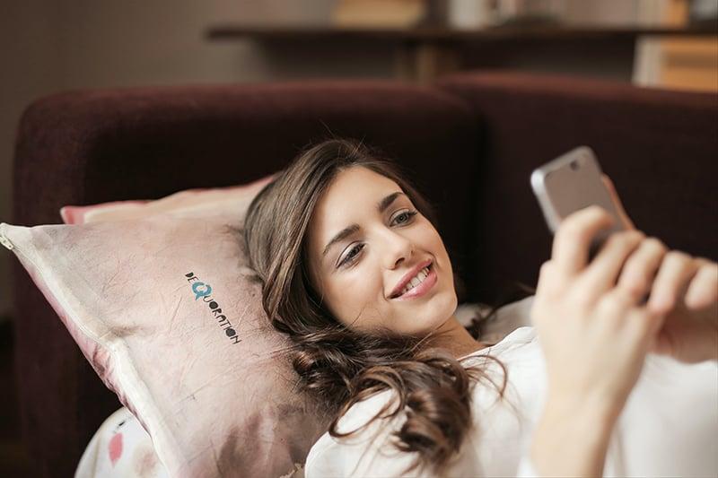 eine lächelnde Frau, die ihr Smartphone benutzt, während sie auf dem Sofa liegt