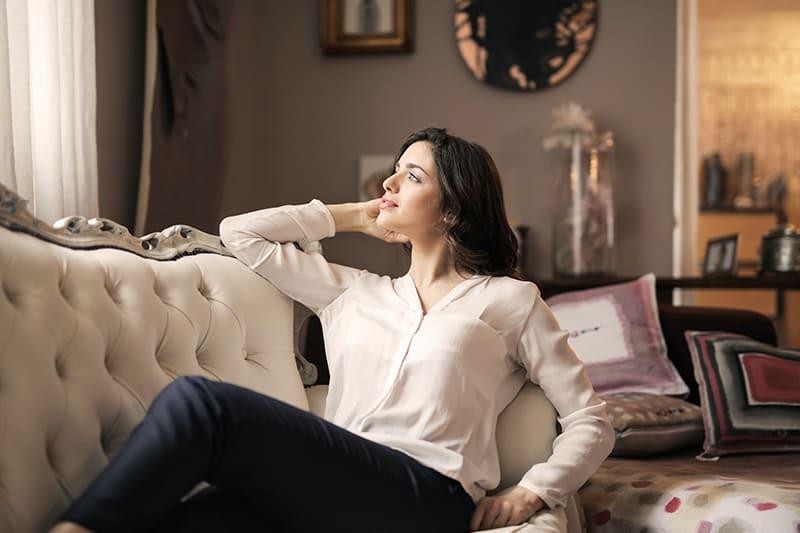 eine lächelnde Frau, die auf dem Sofa sitzt und zu einem Fenster schaut