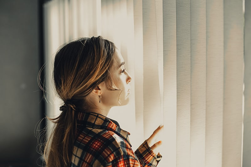 eine nachdenkliche Frau, die am Fenster steht und durch die Jalousien schaut