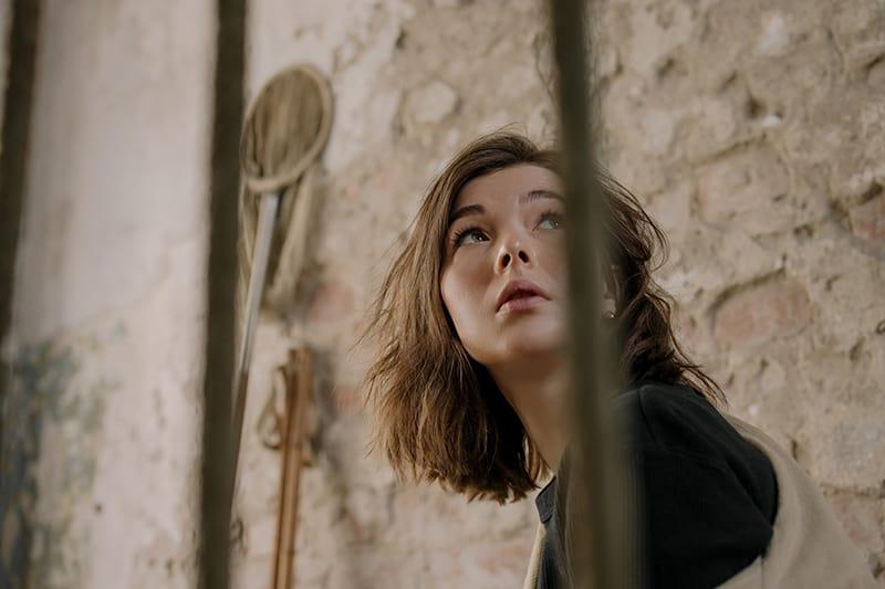 eine nachdenkliche Frau, die in der Nähe der braunen Wand sitzt
